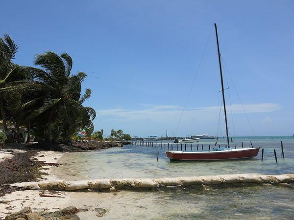 Strand met zeilboot op het eiland Caye Caulker in Belize.